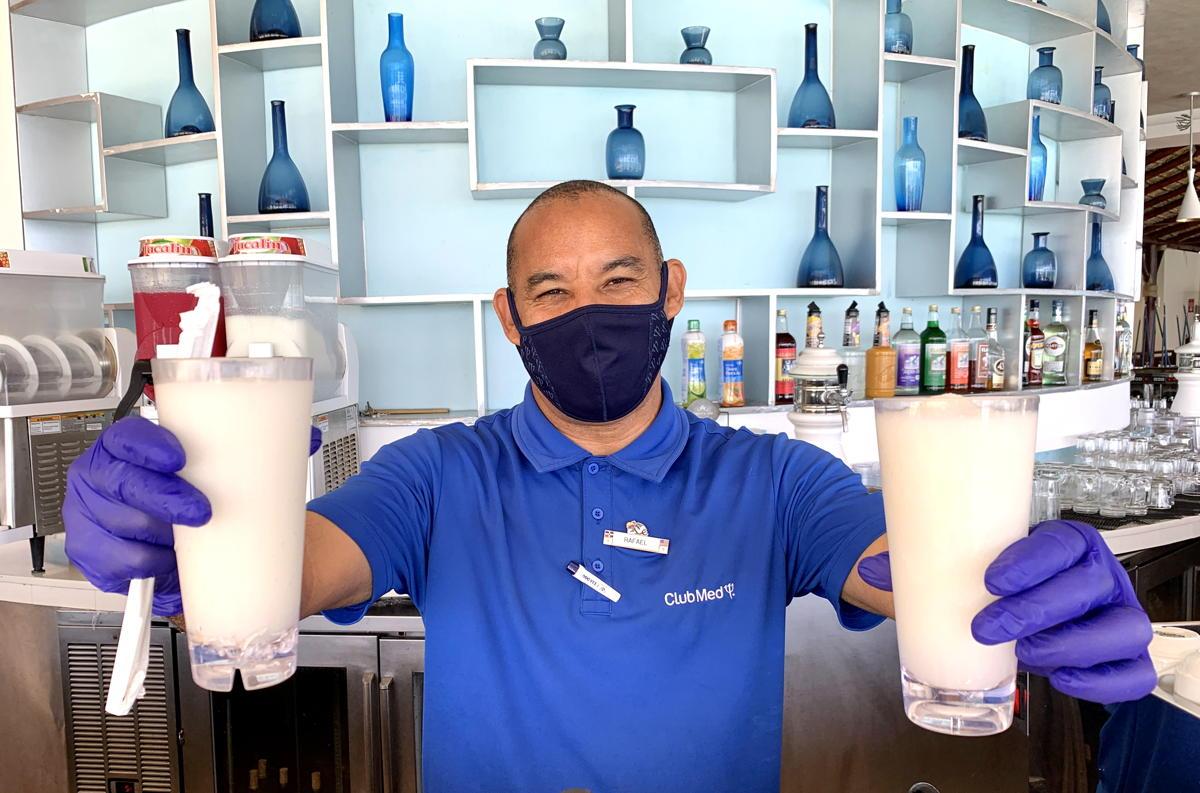 Un barman masqué au bar de plage Indigo.