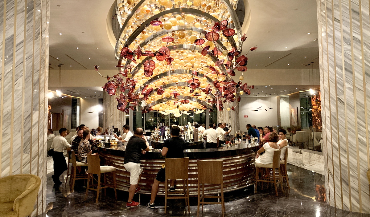 COCKTAIL TIME. A glass-blown chandelier hangs above the lobby bar at The Grand at Moon Palace.