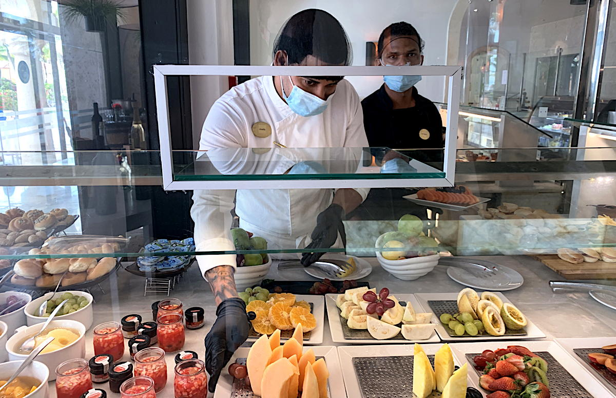 At the buffet, food now plated and served through a rectangular hand-off window. (Pax Global Media)