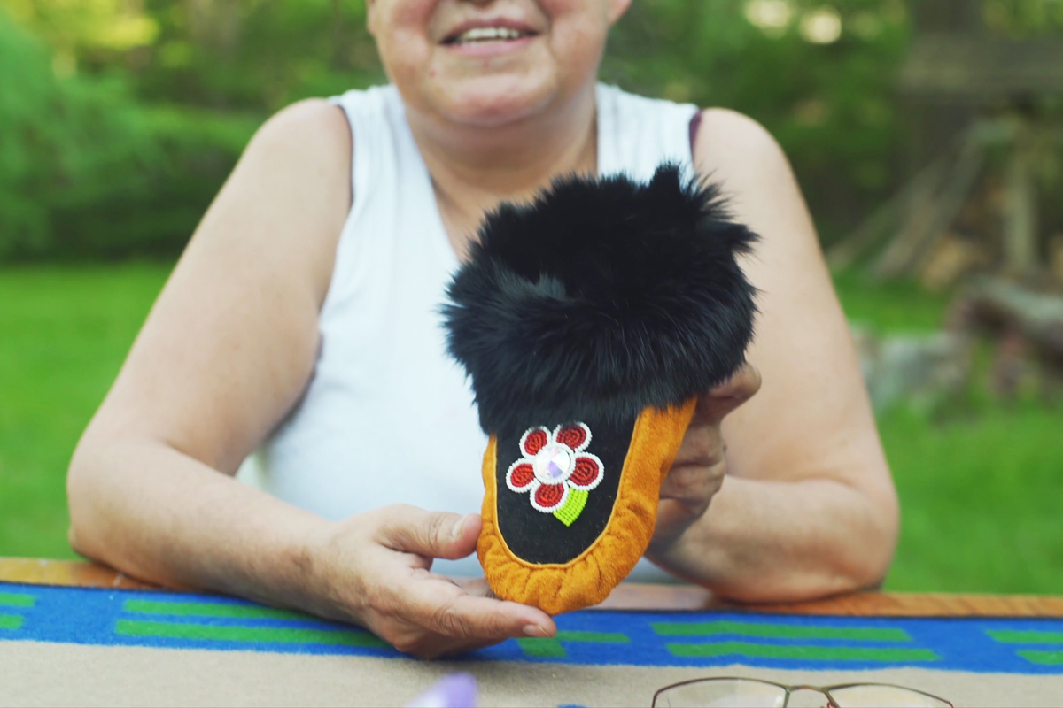 Roberta Anderson, a Cree elder and moccasin maker, holds up a finished moccasin.